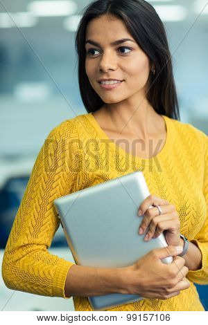 Portrait of a casual pretty businesswoman holding tablet computer in office and looking away