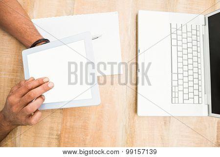 Hands using blank screen tablet on wooden desk
