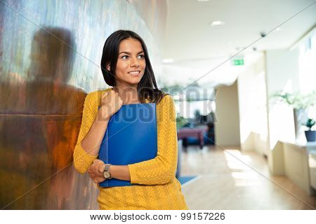 Portrait of a happy businesswoman standing with folder in hallway and looking away