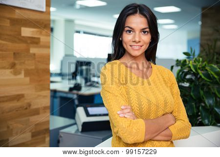 Portrait of a smiling businesswoman standing with arms folded in office and looking at camera