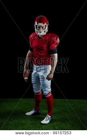 Portrait of american football player holding football against black background