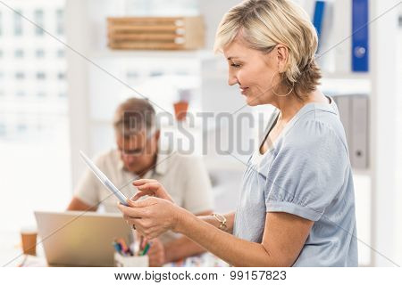 Profile view of a businesswoman scrolling on a tablet at office