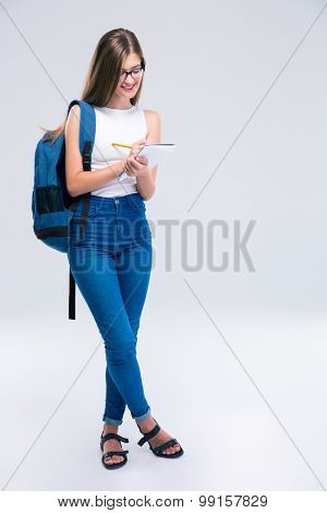 Full length portrait of a smiling female teenager writing notes in notebook isolated on a white background