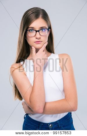Portrait of a thoughtful girl in glasses standing isolated on a white background. Looking at camera
