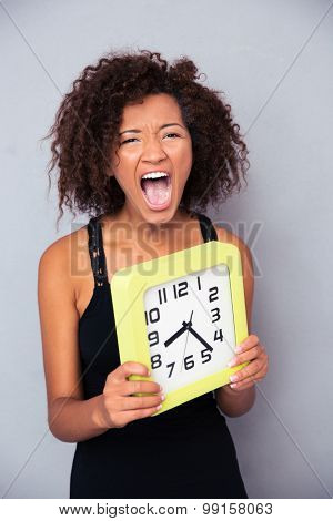 Portrait of african woman holding clock and shouting over gray background