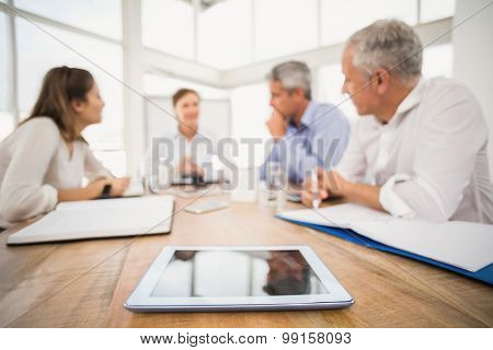 Tablet in front of talking business people in the office