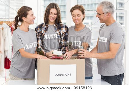 Smiling volunteers sorting donation box in the office