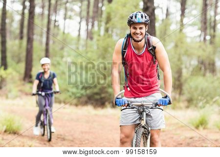 Happy young biker couple looking at camera in the nature