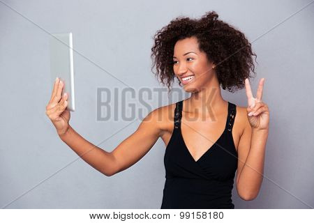 Portrait of a smiling afro american woman making video call on tablet computer over gray background