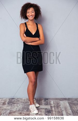Full length portrait of a happy african woman standing with arms folded on gray background. Looking at camera