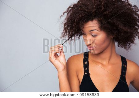 Portrait of a young afro american woman touching her hair over gray background