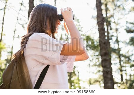 Smiling brunette hiker looking through binoculars in the nature