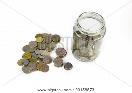 Coins In And Outside A Glass Jar Isolated On White Background