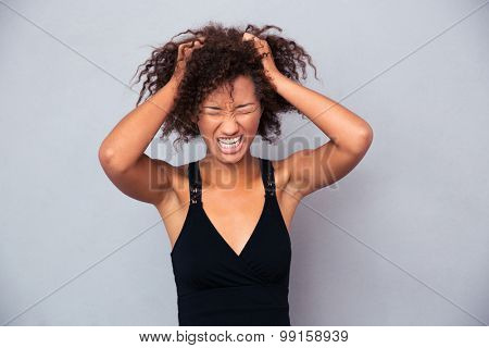 Portrait of afro american woman screaming over gray background