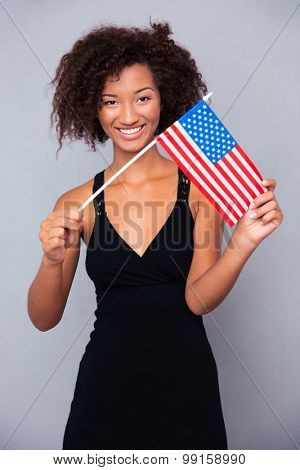 Portrait of a happy afro american woman holding USA flag over gray background and looking at camera