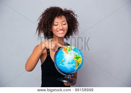 Portrait of a smiling afro american woman holding globe over gray background