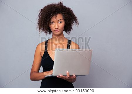 Portrait of a beautiful afro american woman using laptop over gray background. Looking at camera
