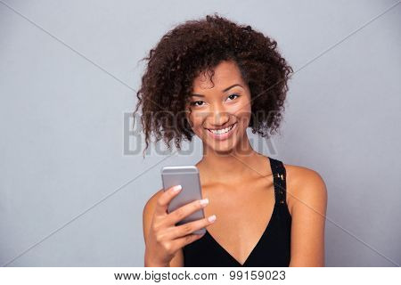 Portrait of a cheerful afro american woman using smartphone over gray background and looking at camera