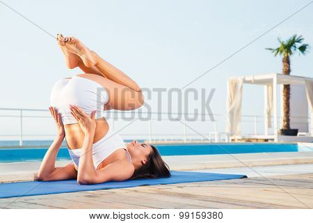 Portrait of a young woman making yoga exercises outdoors