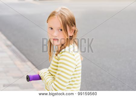 Close up portrait of adorable young 8 years old girl leaning on his scooter