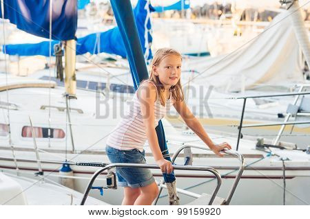 Cute little girl resting on a yacht in a port on a nice summer day