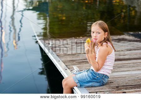Outdoor portrait of a cute little girl, eating ice cream, resting by the lake