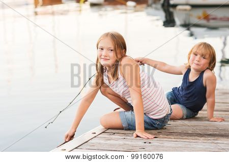 Cute kids, little girl and her brother, having fun outdoors, playing by the lake, resting on a pier