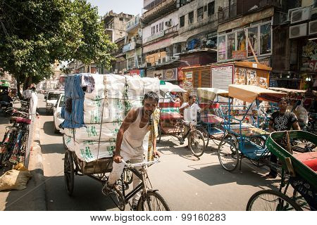 Rickshaw carrying heavy cargo n the street of Old Delhi