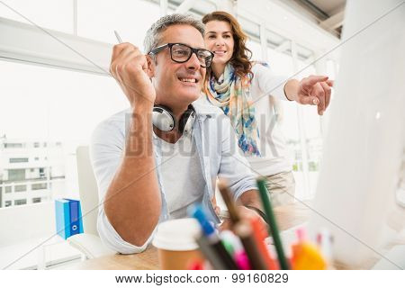Two casual designers working with computer in the office