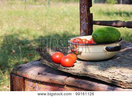 Tomatoes And Cucumber In The Bowl On Old Chair