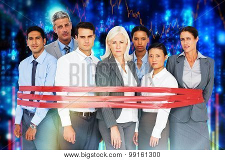 Unhappy business people surrounding by red strip against stocks and shares