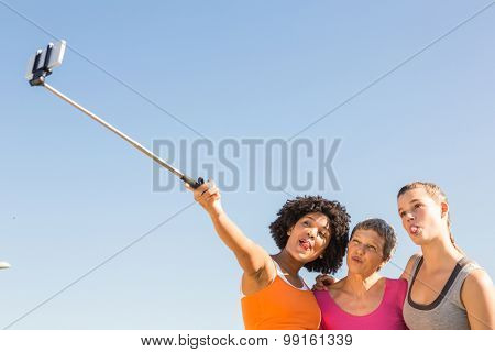 Sporty women posing and taking selfies with selfiestick at promenade