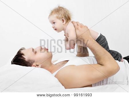 father and his two months old baby, in bed at home