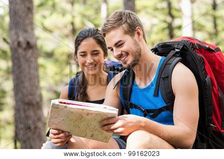 Young happy joggers looking at map in the nature