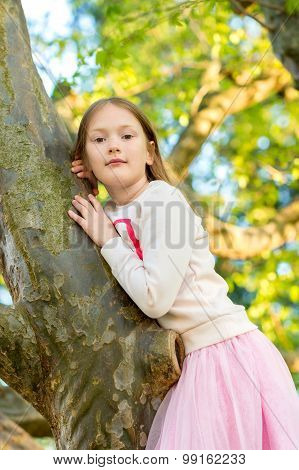 Cute little girl playing in the park, climbing on the tree