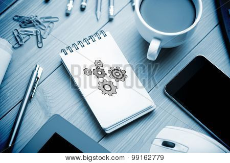 Cogs against notepad on desk