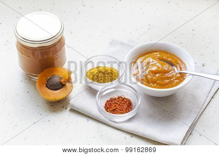 Apricot curry in a glass jar, spices and fresh apricots, selective focus