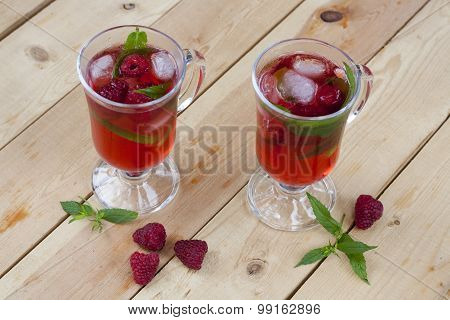 Raspberries fresh drinks with ice and mint on wooden table, selective focus