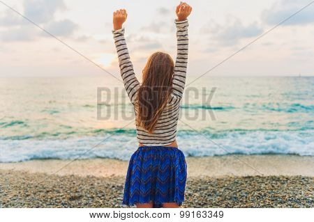 Little girl resting on the beach, watching the sunset