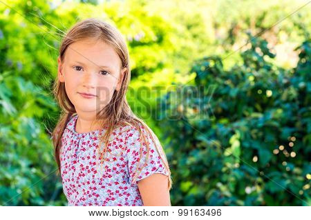 Outdoor portrait of a cute little girl playing in a garden on a nice sunny day