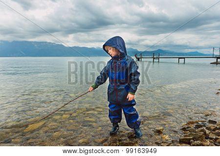 Cute little boy playing by the lake, pretending fishing