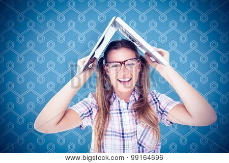 Geeky hipster holding her laptop over her head against background