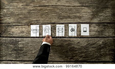 High Angle View Of Businessman Laying Out White Cards With Communication And People Icons