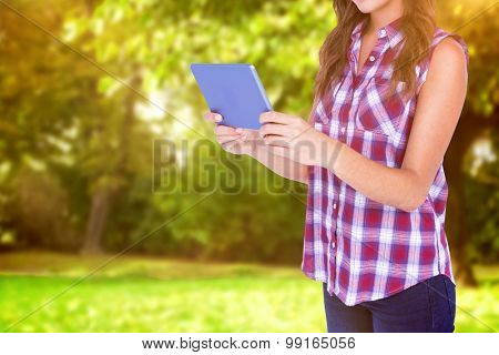 Happy pretty brunette using tablet computer against trees and meadow in the park
