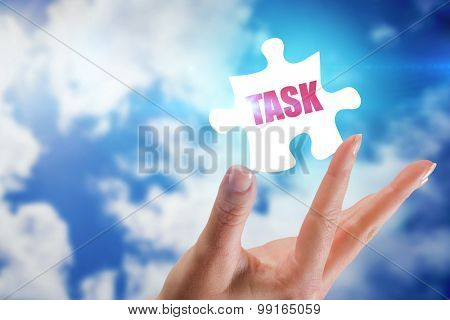 The word task and hand showing against bright blue sky with clouds