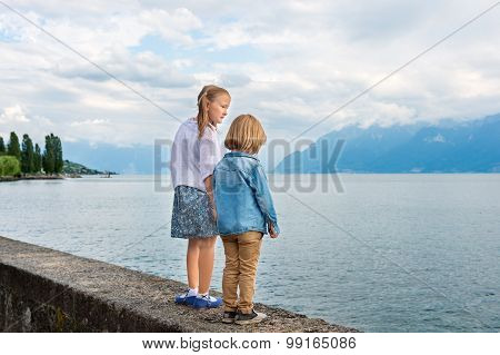 Outdoor portrait of cute little kids walking by the beautiful lake
