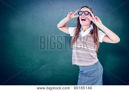 Happy geeky hipster dancing against green chalkboard