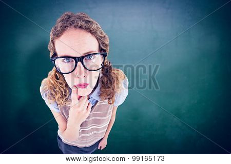 Geeky hipster woman thinking with hand on chin against green chalkboard