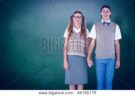 Geeky hipster couple holding hands against green chalkboard