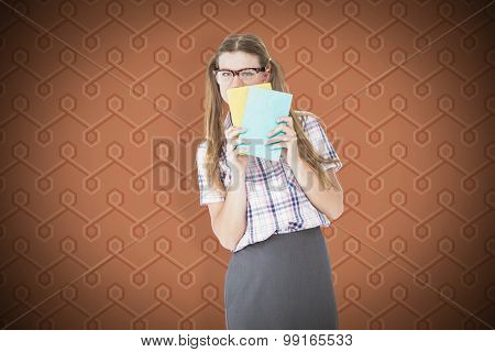 Geeky hipster hiding her face behind notepad against background